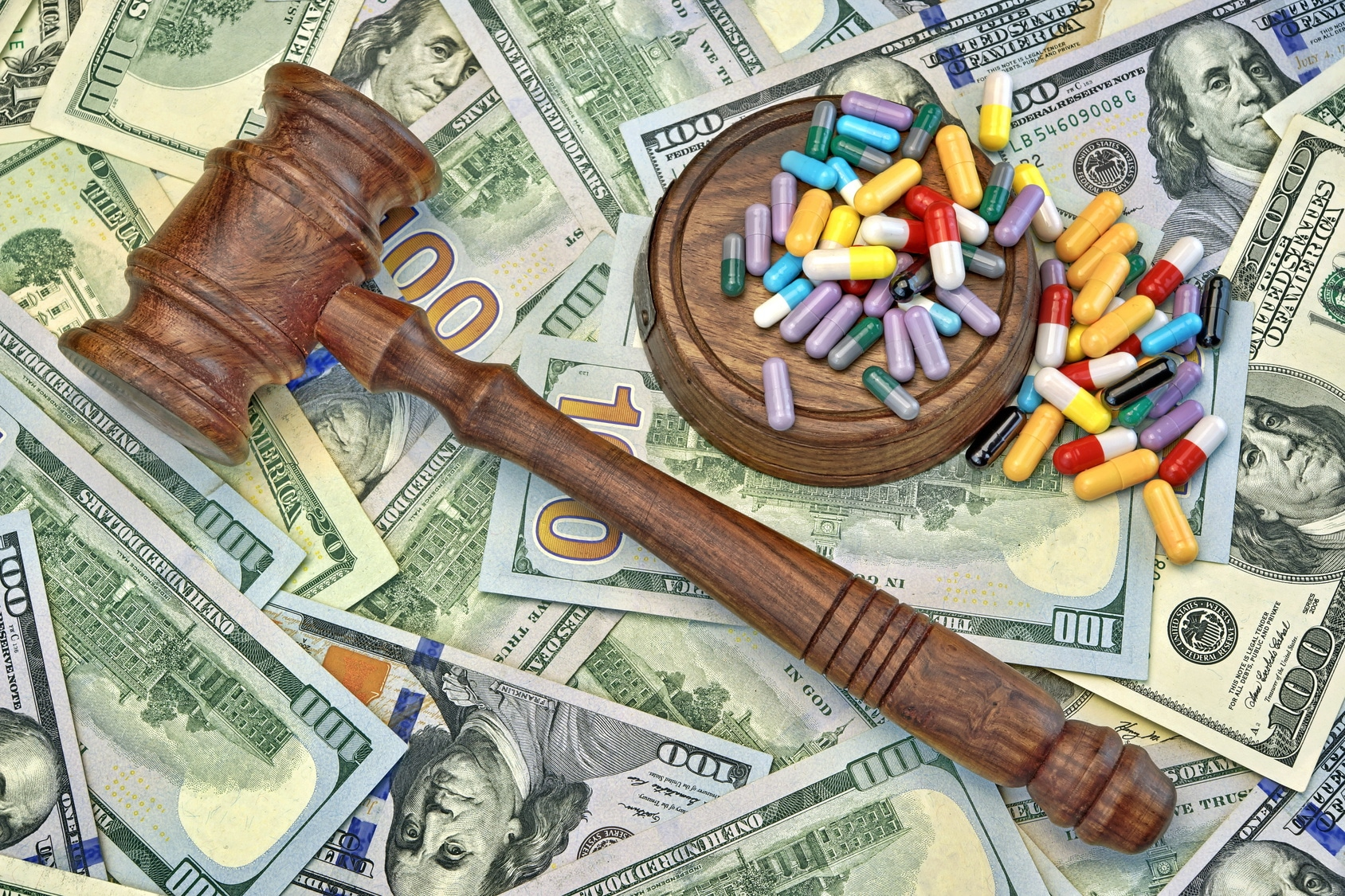 Wood Judges Gavel And Scattered Colorful Drugs On The Dollar Cash Background, Overhead View, Concept For Medical Negligence, Bail, Monetary Compensation, Drugs Falsification